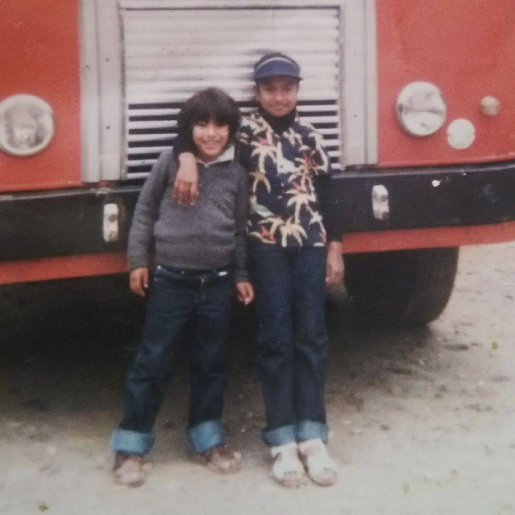 Brother and sister posing in front of a bus