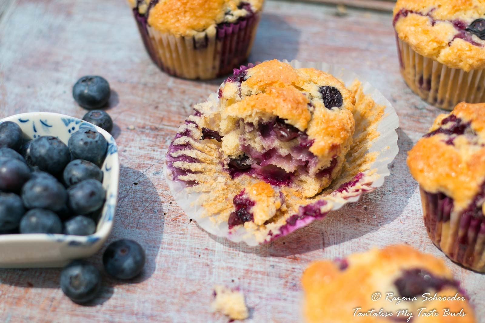 Blueberry muffins broken to reveal the soft crumb and moist texture