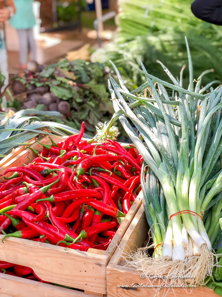 Red chillis and spring onions on a farmers market table