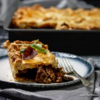 Slice of Cape Malay Pepper Steak Pie with pie tray in back